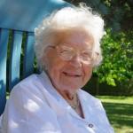 lachende ältere Dame im Gartenstuhl