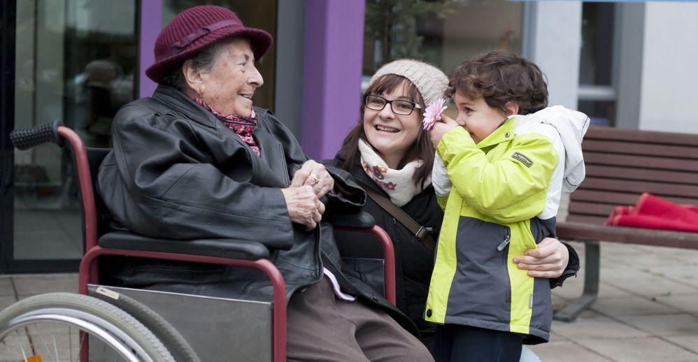 Ältere Dame im Rollstuhl, junge Frau und kleiner Junge, der Blume überreicht
